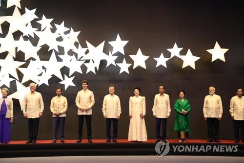 资料图片:当地时间11月12日下午,在马尼拉SMX会展中心,韩国总统文在寅(左五)和第一夫人金正淑女士(右五)与各国领导人在东盟50周年晚宴合影。(韩联社)