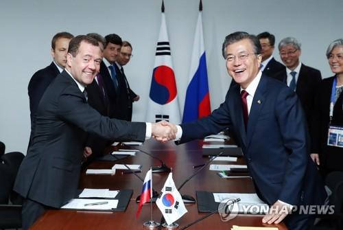 马尼拉时间11月14日上午,在菲律宾国际会展中心,文在寅(右)和梅德韦杰夫在双边会谈上握手。(韩联社)