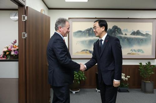 11月22日,韩国统一部长官赵明均(右)同到访的联合国世界粮食计划署执行主任戴维・比斯利举行会晤,图为双方握手合影。(韩联社/统一部提供)