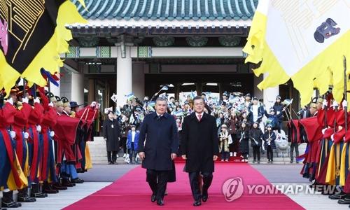 11月23日,在青瓦台,韩国总统文在寅(右)同到访的乌兹别克斯坦总统沙夫卡特・米尔济约耶夫检阅仪仗队。(韩联社)