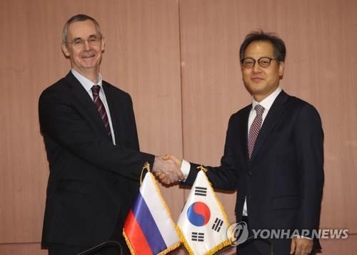 11月29日上午,在首尔,金英俊(右)与巴尔宾在韩俄北极协商会上握手。(韩联社)