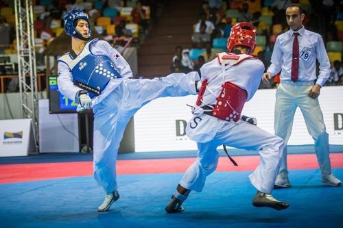 当地时间12月3日,在科特迪瓦阿比让举行的世界跆拳道大奖赛68公斤级比赛中,李大勋(左)对战俄罗斯选手丹尼斯耶科。(韩联社/世界跆拳道联盟提供)