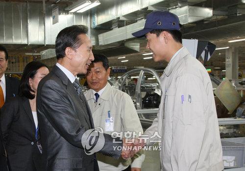 资料图片:2008年5月29日,在北京现代汽车工厂,李明博与一位员工握手.