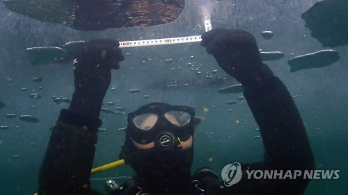 资料图片:华川山鳟鱼庆典工作人员测量冰层厚度(韩联社/华川郡提供)