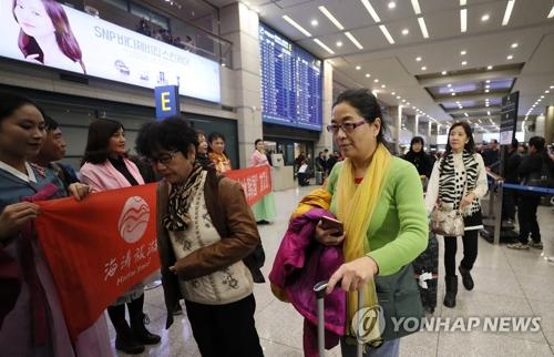 资料图片:2017年12月2日,中国团体游客通过仁川机场入境韩国。(韩联社)