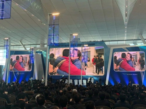 1月12日下午,在仁川机场第二航站楼,出席航站楼启用仪式的人士在观看宣传视频。(韩联社)