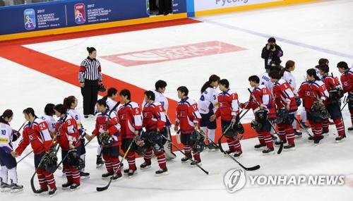 资料图片:2017年4月6日,在韩国江原道江陵冰球中心,韩朝女子冰球代表队队员们在2017国际冰联女子冰球世锦赛乙级A组韩朝大战结束后握手致意。(韩联社)