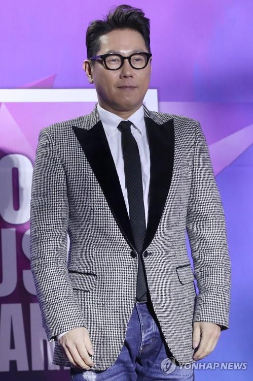 1月25日下午,在首尔高尺天空巨蛋,歌手尹钟信在第27届首尔歌谣大赏的红毯上摆出造型供记者拍照。(韩联社)