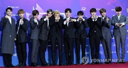 1月25日下午,在首尔高尺天空巨蛋,韩国男团Wanna One在第27届首尔歌谣大赏的红毯上摆出造型供记者拍照。(韩联社)