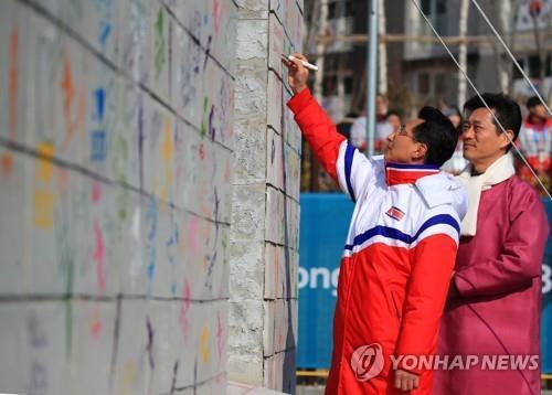 朝鲜体育代表团团长元吉友(左)在奥林匹克休战墙上签名。(韩联社)
