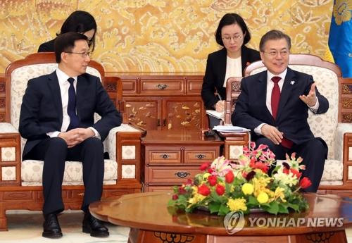 2月8日,在青瓦台,韩国总统文在寅(右)会见中共中央政治局常委韩正。(韩联社)