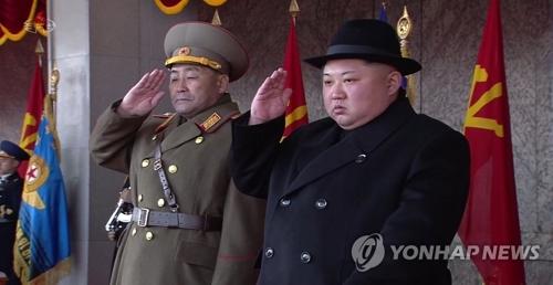 2月8日朝鲜央视录播建军节阅兵式,图为在阅兵式主席团上,金正角(左)与金正恩并排站立行礼。图片仅限韩国国内使用,严禁转载复制。(韩联社/朝鲜央视截图)