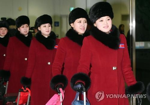 """资料图片:2月7日上午,在京畿道坡州市都罗山南北出入境事务所(CIQ),身着红衣、胸戴朝鲜""""国旗""""徽章的朝鲜拉拉队成员走入韩国境内。(韩联社/联合采访团)"""