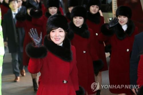 2月12日,在首尔一家酒店,朝鲜艺术团团员乘车前挥手致意。(韩联社)
