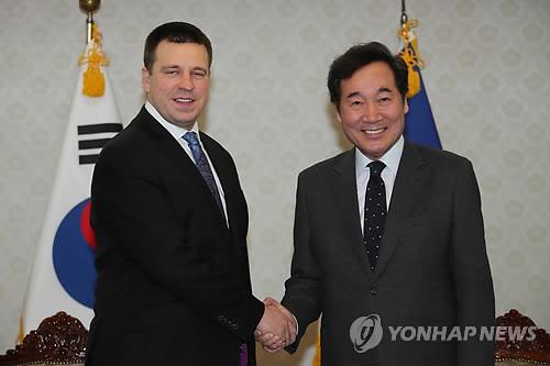2月14日上午,在首尔中央政府大楼,韩国国务总理李洛渊(右)与到访的爱沙尼亚总理于里・拉塔斯握手。(韩联社)