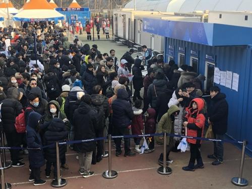 2月14日,在江陵关东冰球中心,前来观看女子冰球小组赛韩朝联队与日本队比赛的观众在排队买票。(韩联社)