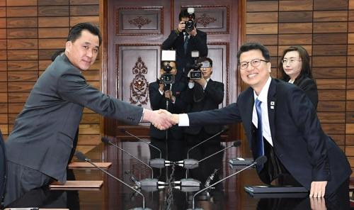 2月27日上午,在板门店,李柱泰(右)和黄忠诚在会谈前握手。(韩联社/韩统一部提供)