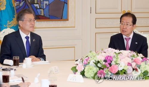 3月7日下午,在青瓦台,韩国总统文在寅邀请韩国朝野五党党首在青瓦台举行午餐会晤。图为文在寅(左)与自由韩国党党首洪准杓。(韩联社)