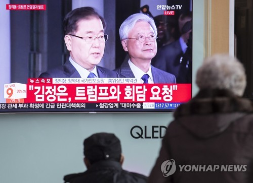 3月9日上午,在首尔站,市民收看郑义溶介绍与特朗普会晤内容的新闻。(韩联社)