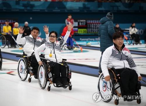 3月13日,在江陵冰球中心,韩国队在2018平昌冬残奥会轮椅冰壶小组循环赛中以11:7完胜芬兰队。图为韩国选手徐淳锡(前起)、方敏子、车在宽(均为音译)获胜后开心地向观众挥手致意。(韩联社)