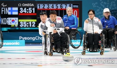 3月13日,在江陵冰球中心,韩国队选手车在宽(音)在2018平昌冬残奥会轮椅冰壶小组循环赛中投掷冰壶。(韩联社)