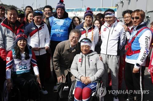 3月14日上午,在平昌残奥越野滑雪预赛后,文在寅与韩国选手们合影。(韩联社/韩总统府青瓦台)