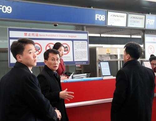 资料图片:崔强一(中间)一行正在办理登机手续。(韩联社)