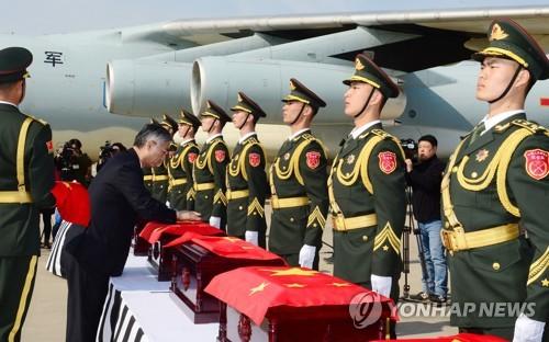 资料图片:2017年3月,在仁川机场,中国驻韩大使邱国洪为韩战中国军人遗骸棺椁覆盖五星红旗。(韩联社)