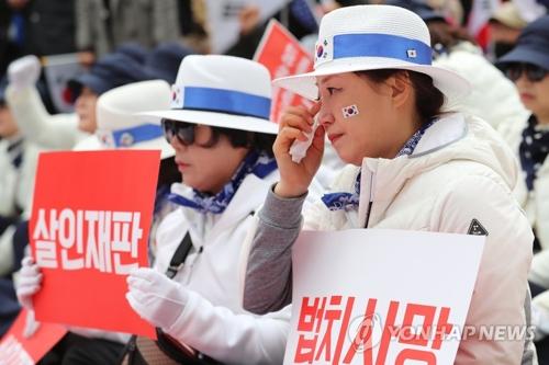 4月6日下午,首尔中央地方法院对韩国前总统朴槿惠作出一审宣判,判处有期徒刑24年,罚款180亿韩元。图为朴槿惠支持者得知判决结果后失声哭泣。(韩联社)