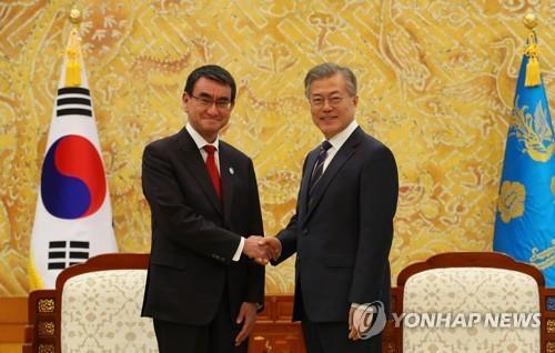 4月11日下午,在韩国青瓦台,总统文在寅(右)接见到访的日本外务大臣河野太�O。图为两人在会晤前握手合影。(韩联社)
