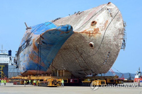 """资料图片:2017年4月11日下午,在木浦新港,工作人员正将模块运输车抽离""""世越""""号船体。(韩联社)"""