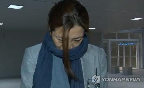 4月15日凌晨,在仁川机场,赵显�G走下从岘港起飞的大韩航空K464航班,面对媒体低头问答。(韩联社/MBC电视台画面)