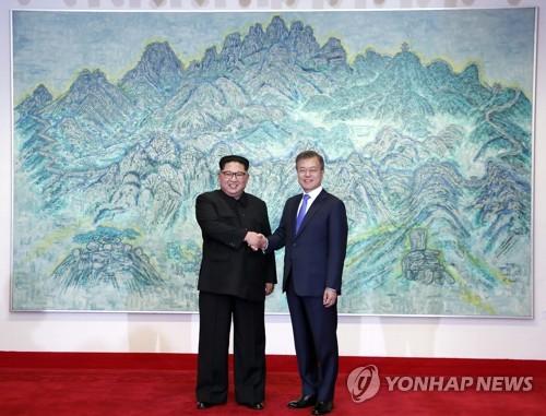 """4月27日,在韩朝边境板门店韩方一侧的""""和平之家"""",文在寅(右)和金正恩亲切握手合影。(韩联社)"""