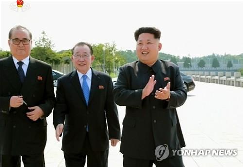 资料图片:金桂官站在金正恩(右)和朝鲜外相李洙墉之间。图片仅限韩国国内使用,严禁转载复制。(韩联社/朝鲜中央电视台截图)