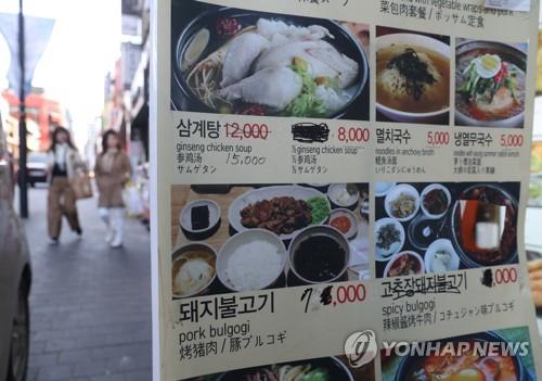资料图片:3月18日,在首尔明洞某餐厅门外,价目表上的餐品价格纷纷上涨。(韩联社)