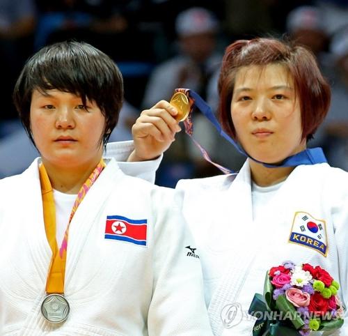 资料图片:站在2014年亚运会冠亚军领奖台上的韩朝女子柔道运动员(韩联社)