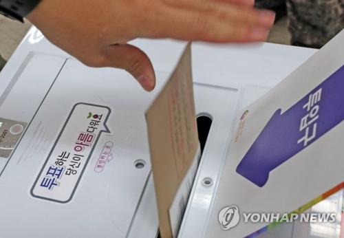 6月8日上午,在江原道春川市新北邑事务所投票站,一名军人投出神圣一票。(韩联社)