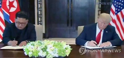 6月12日上午,在新加坡圣淘沙岛嘉佩乐酒店,美国总统特朗普(右)和朝鲜国务委员会委员长金正恩签署联合公报。(韩联社/新加坡《海峡时报》截图)