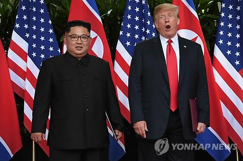 6月12日,在新加坡,金正恩(左)与特朗普签署联合声明后接受媒体拍照。(韩联社/法新社)