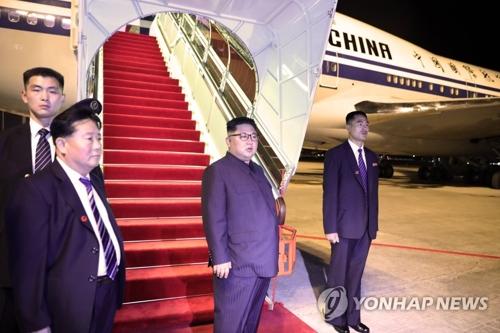 资料图片:6月12日,在新加坡樟宜机场,金正恩(右二)准备登机。(韩联社/新加坡通信及新闻部提供)
