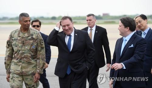 6月13日,在京畿道平泽市的驻韩美军空军基地,美国国务卿蓬佩奥(前排居中)下机后与接机人员交谈。前排左为韩美联合司令部司令文森特・布鲁克斯,右为美国驻韩使馆临时代办马克・纳珀。(韩联社)