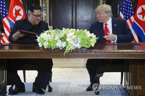 6月12日,在新加坡,美国总统特朗普(右)同朝鲜国务委员会委员长金正恩在会后签署联合声明。(韩联社/美联社平壤分社)