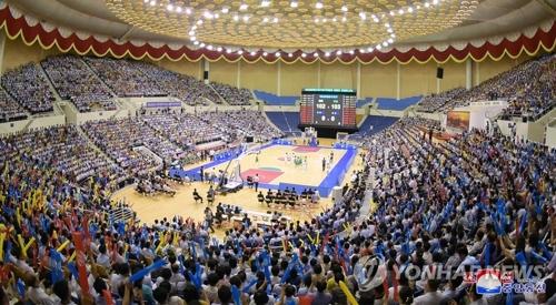 7月4日下午,在平壤柳京郑周永体育馆,韩朝选手混合组成的韩朝统一篮球赛和平队与繁荣队进行男子混合赛。图为现场观众为选手热情加油助威。(韩联社/朝中社)
