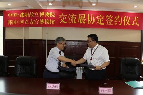 7月4日,在在沈阳故宫博物院,韩国国立古宫博物馆馆长池炳穆(左)和沈阳故宫博物院院长白文煜签署协议后,握手致意。(韩国国立古宫博物馆供图)
