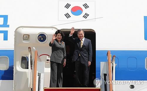 资料图片:7月8日下午,在位于京畿道城南市的首尔机场,韩国总统文在寅(右)和夫人金正淑在专机舷梯上向送行人群挥手致意。文在寅当天启程前往印度新德里,对印度进行为期四天的国事访问。(韩联社)