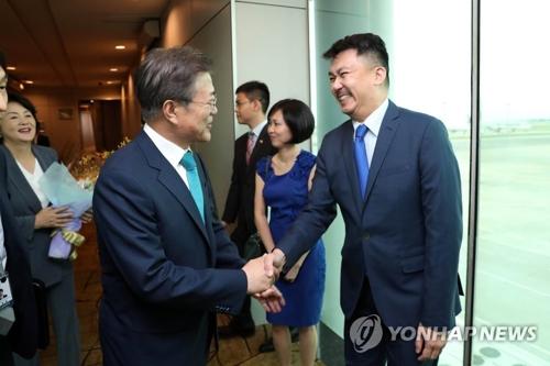 7月11日下午,在新加坡,韩国总统文在寅偕夫人金正淑女士抵达新加坡樟宜机场,开始对新加坡进行为期三天的国事访问。图为文在寅同前来迎接的驻韩新加坡大使叶伟杰(右)握手。(韩联社)