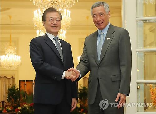 7月12日上午,在新加坡总统府,文在寅(左)和李显龙在首脑会谈上亲切握手。(韩联社)