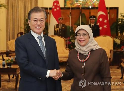 7月12日上午,在新加坡总统府,韩国总统文在寅(左)与新加坡总统哈莉玛・雅各布握手合影。(韩联社)