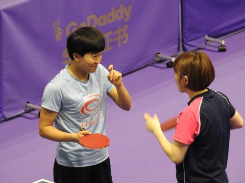 7月16日上午,在韩国大田市韩巴体育馆,备战2018年国际乒联世界巡回赛韩国公开赛女子双打项目的韩朝联队选手徐孝元(右)与金宋依在交谈。(韩联社)
