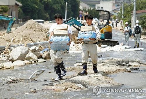 资料图片:7月19日,在日本广岛,志愿者搬运爱心物资。(韩联社)